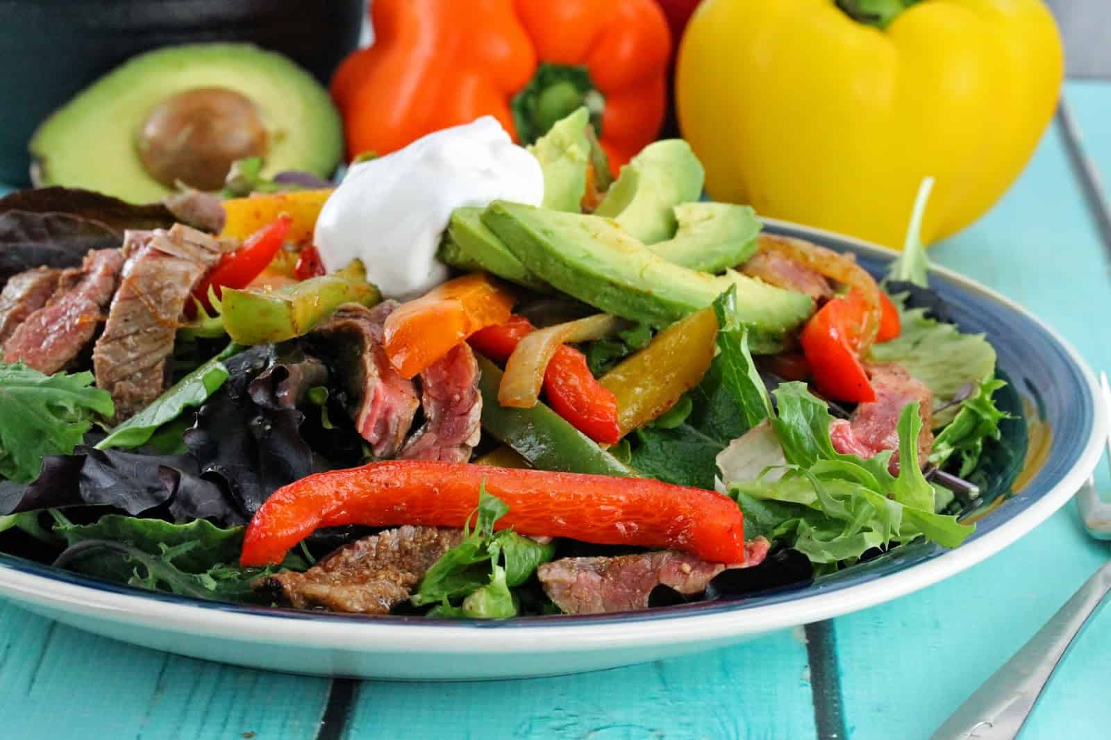 Fajita salad on a blue and white plate.
