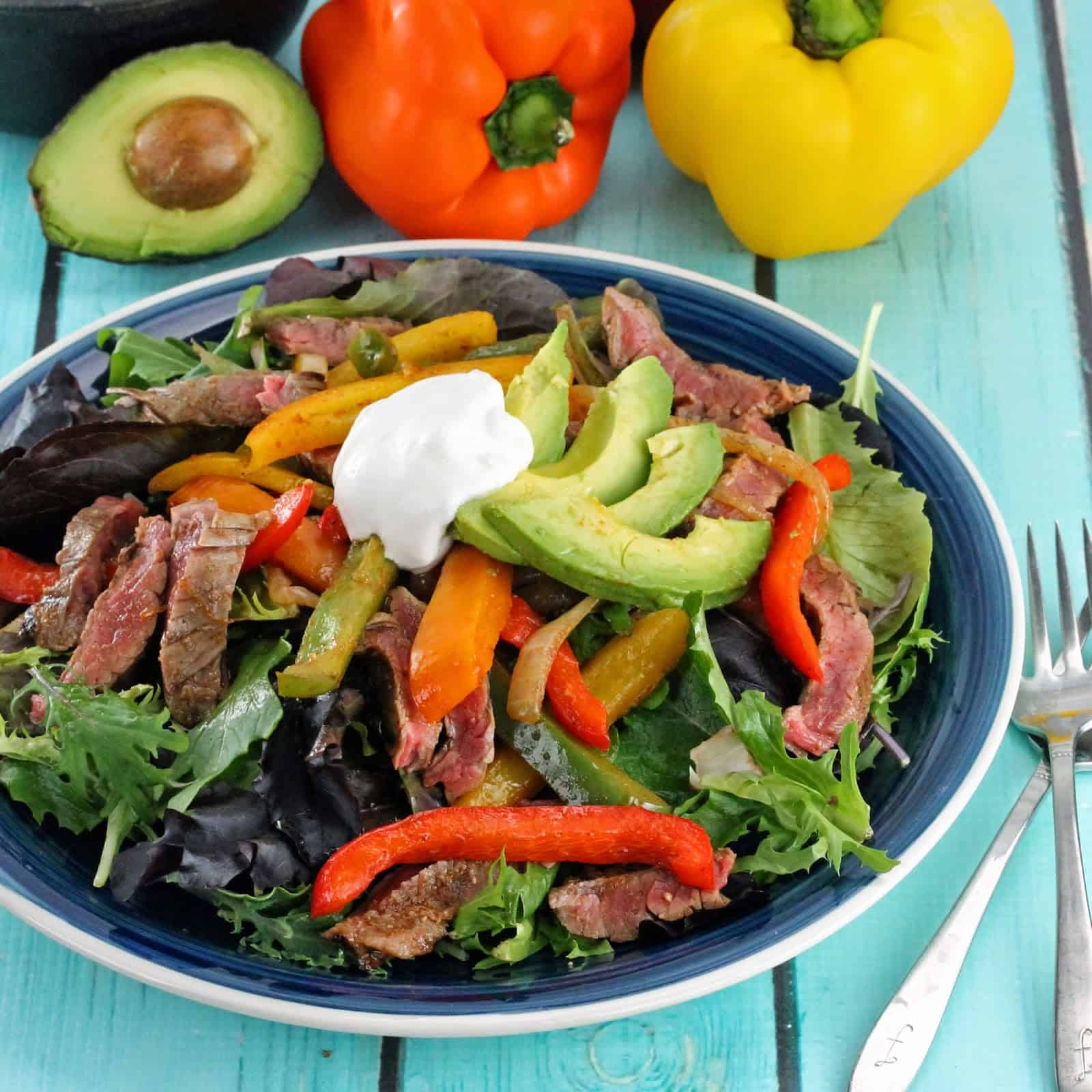 Skinny Fajita Salad served up with grilled flank steak, fresh avocado and bell peppers over a bed of lettuce and topped with a dollop of sour cream