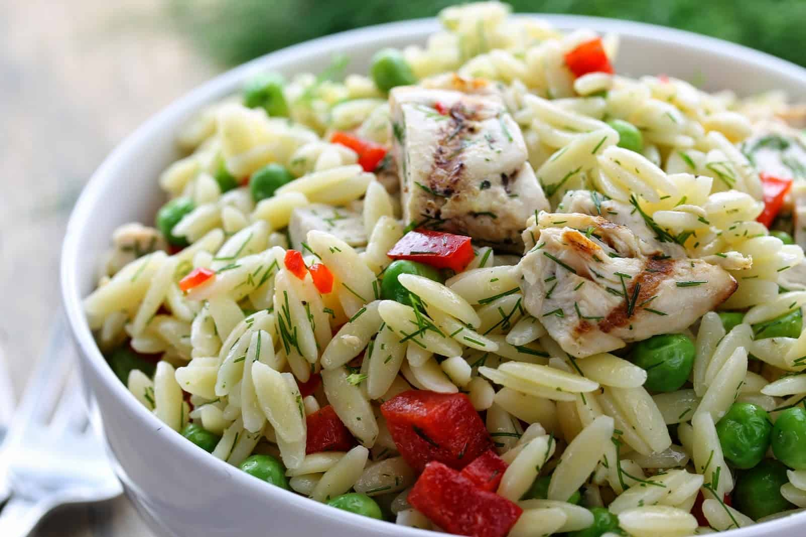 close up of lemon dill chicken with orzo pasta salad in a bowl