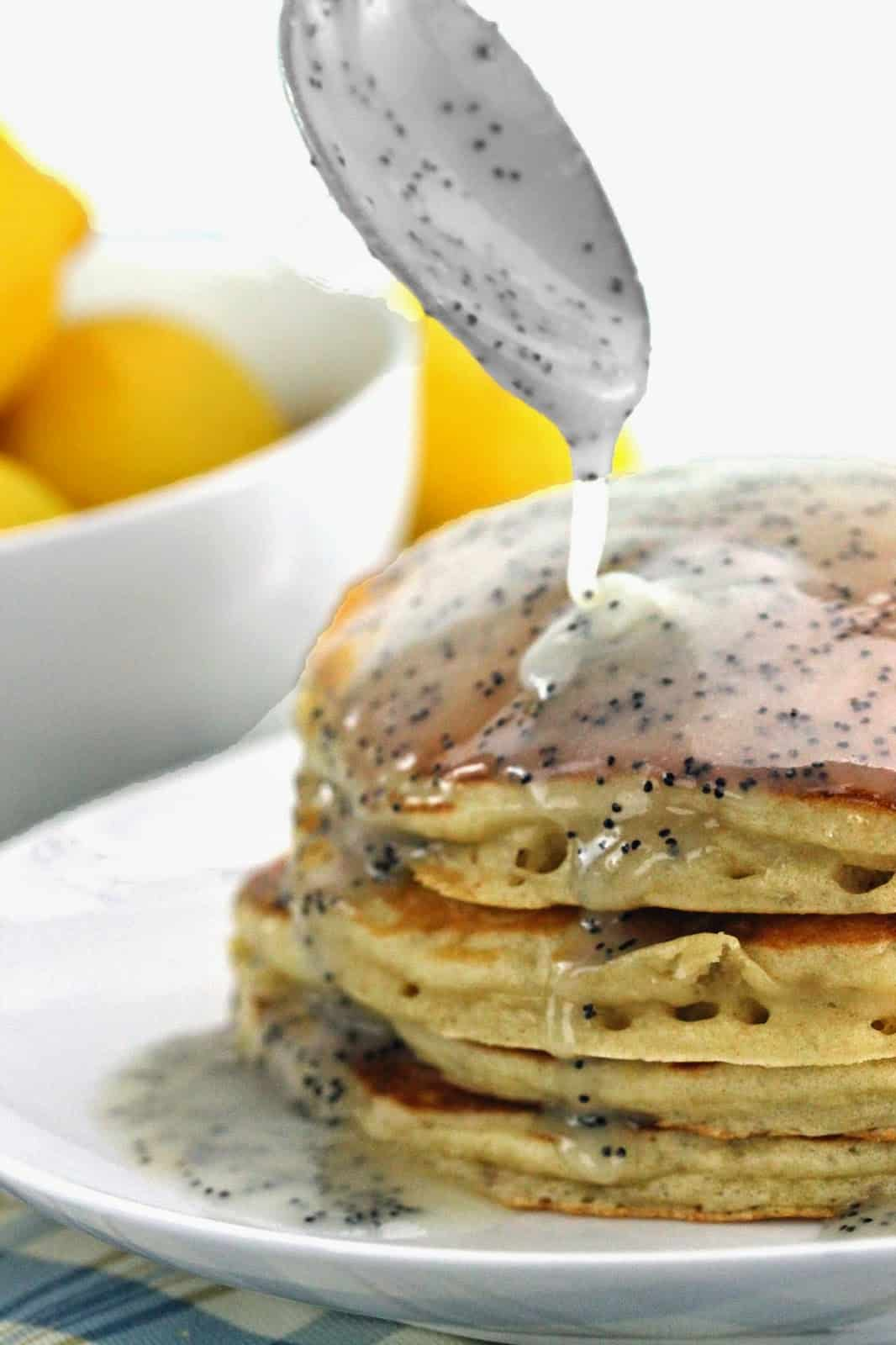 Lemon Poppyseed Buttermilk Syrup being poured on a stack of pancakes.