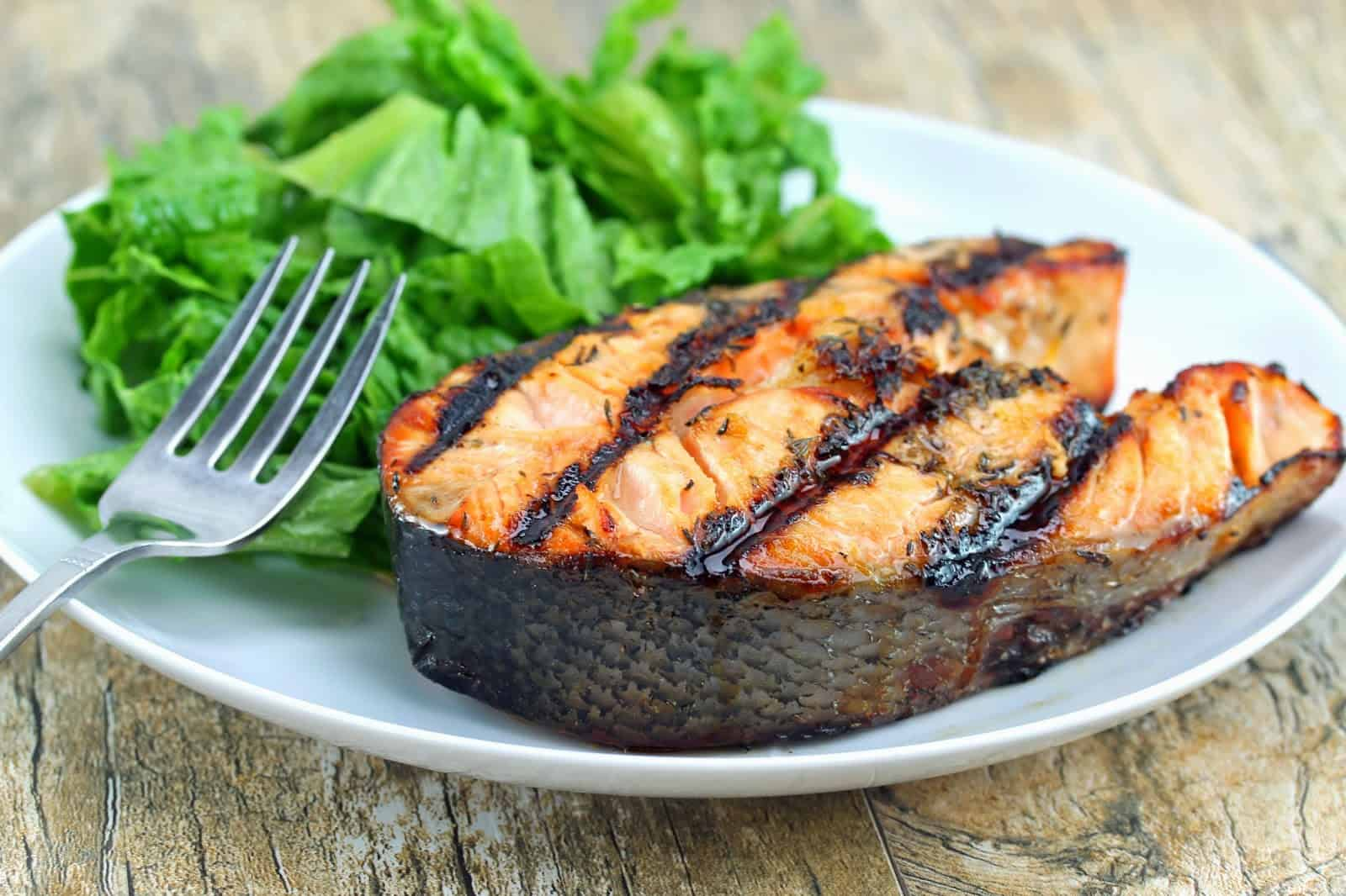 Orange-Ginger Grilled Salmon Steaks on a white plate with a small salad and a fork.