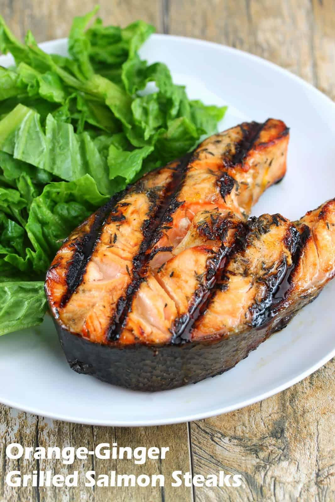 Orange ginger grilled salmon steaks on a white plate with a salad