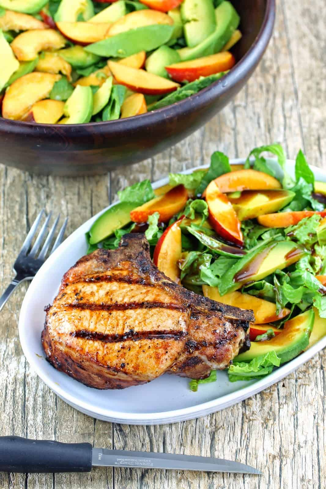 grilled pork chop salad with nectarine and avocado on a white plate
