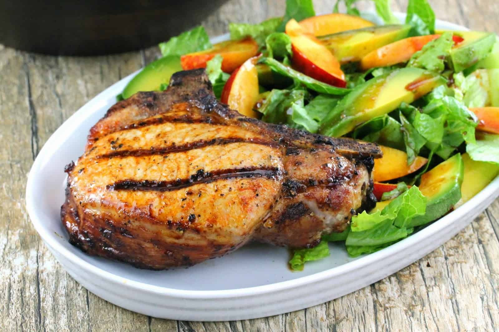 Grilled Pork Chop and a Nectarine and Avocado Salad on a white plate.