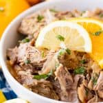A bowl of Slow Cooker Cuban Mojo Pork garnished with chopped fresh cilantro and orange slices
