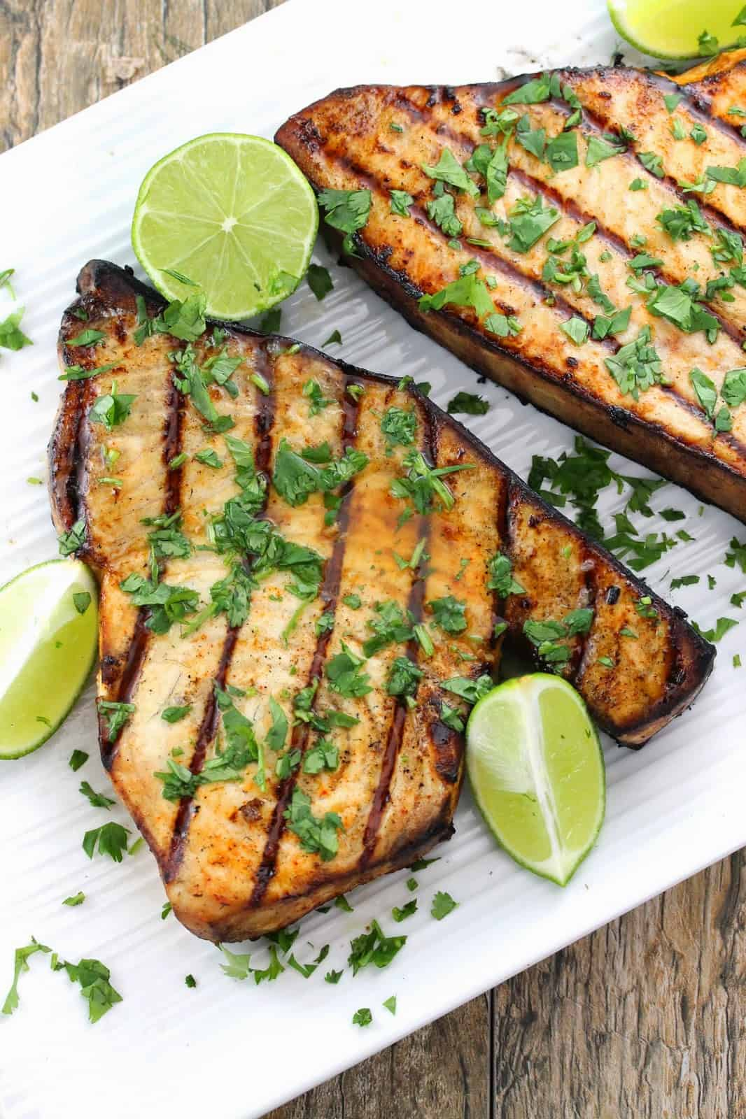Grilled swordfish topped with cilantro and lime wedges