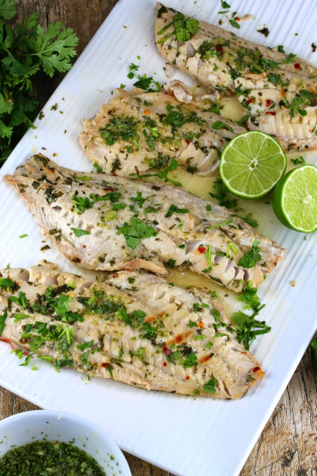 Thai grilled fish with lime wedges on a white serving platter