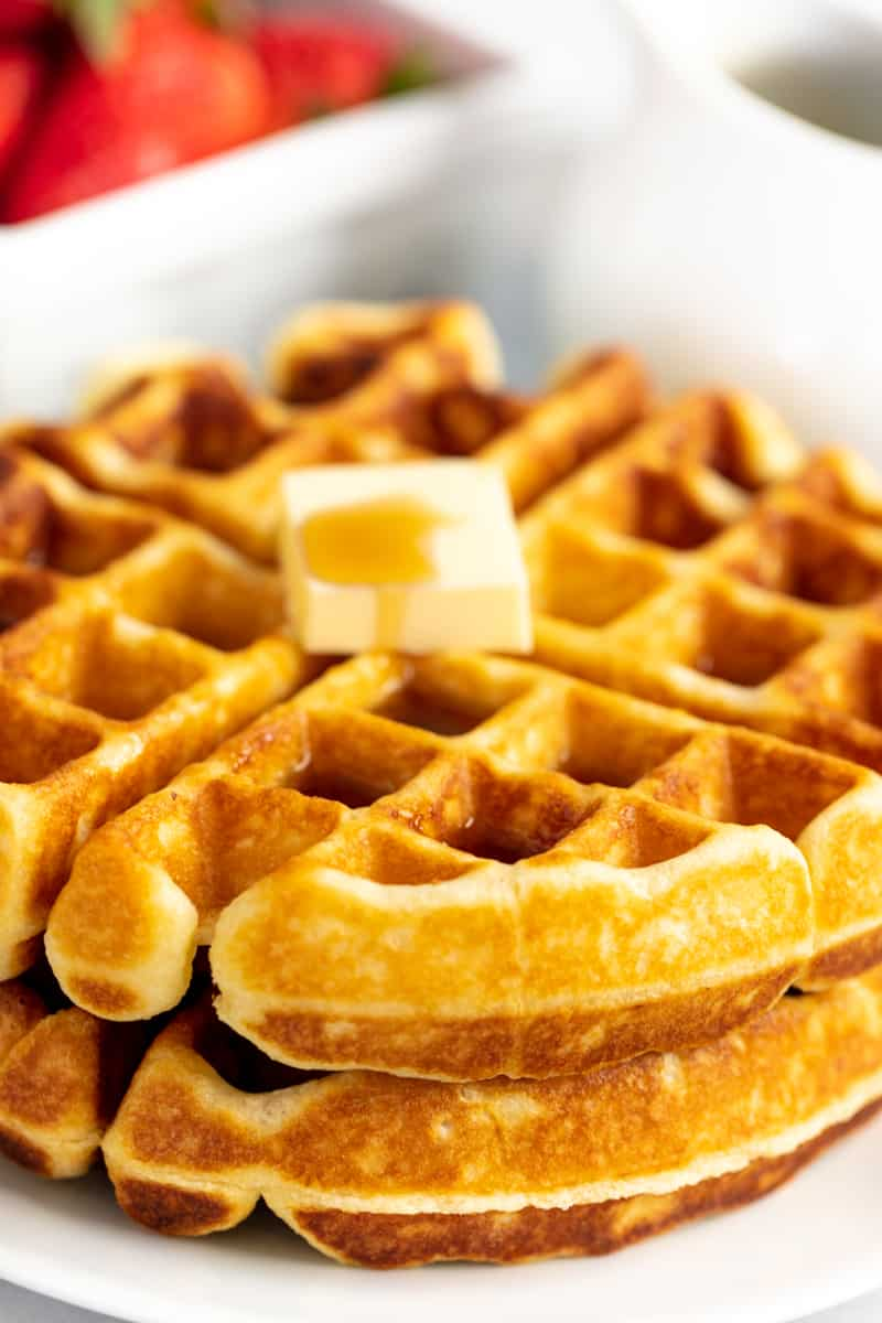 Stack of two waffles with a pad of butter and covered in syrup on a white plate.