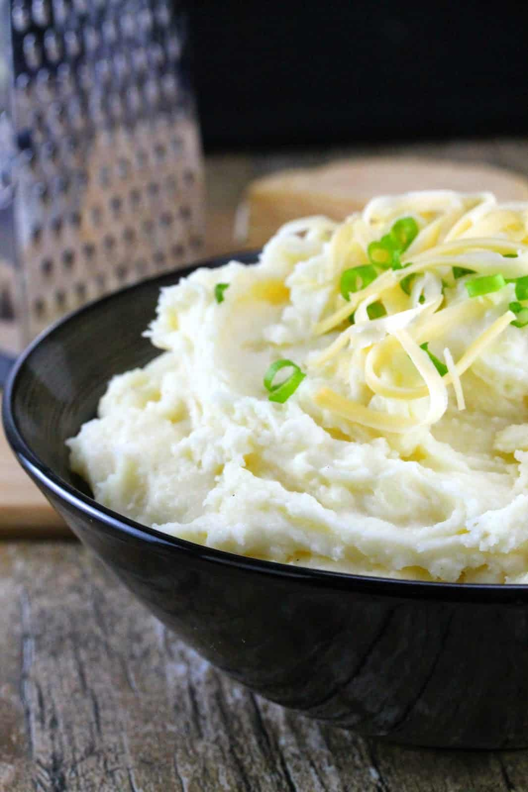 Close up of Smoked Gouda Mashed Potatoes served up with some freshly grated smoked gouda and chopped green onion