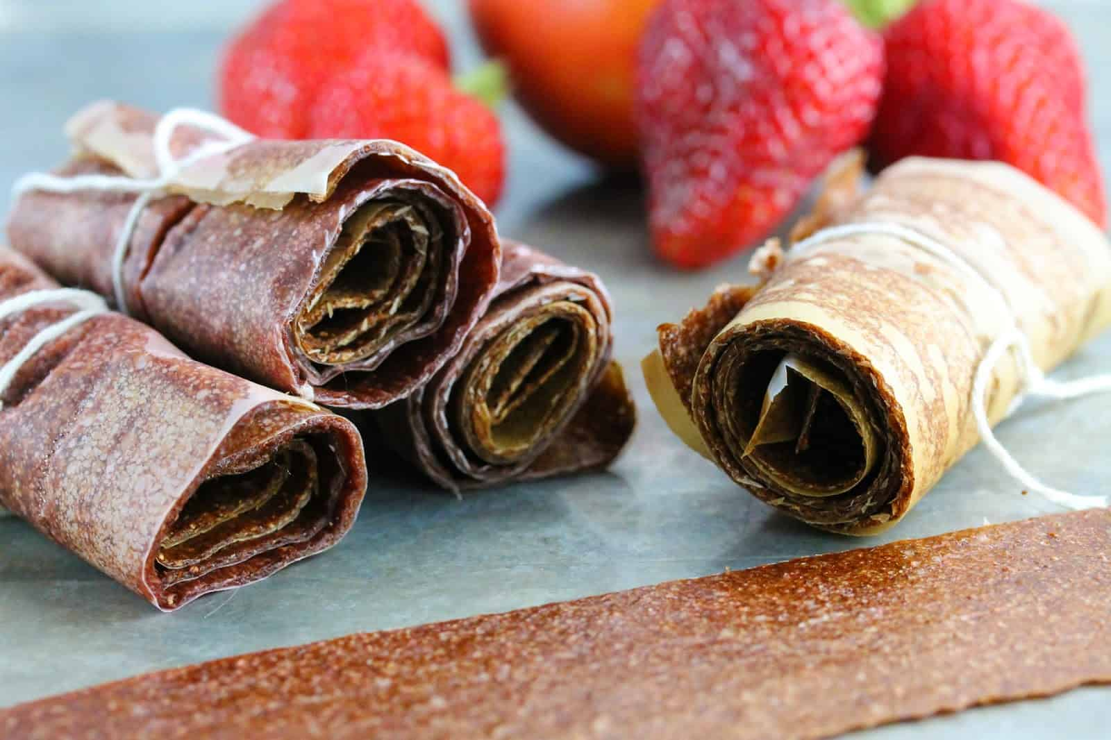 Close up of A stack of No Simmer Strawberry-Nectarine Fruit Roll Ups rolled in parchment paper and tied with a string