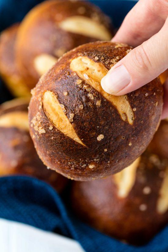 Hand holding a pretzel roll.