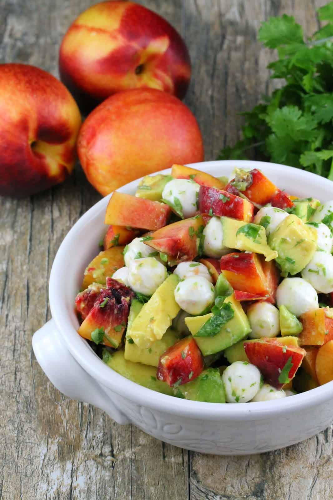 Nectarine and Avocado Fruit Salad in a white bowl sitting next to three nectarines.
