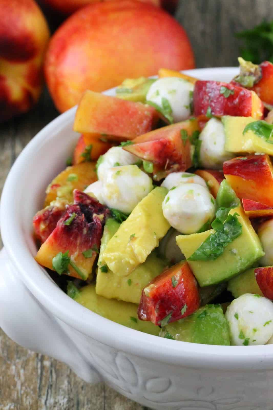 Close up of Nectarine and Avocado Fruit Salad in a white bowl
