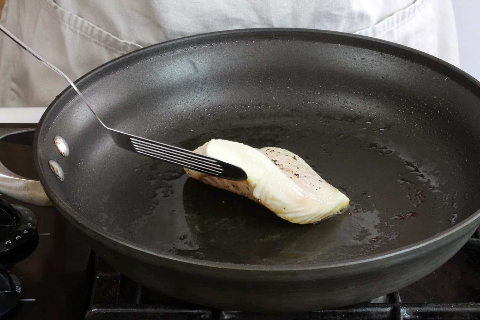 A spatula lifts the filet from the skillet, ready to flip