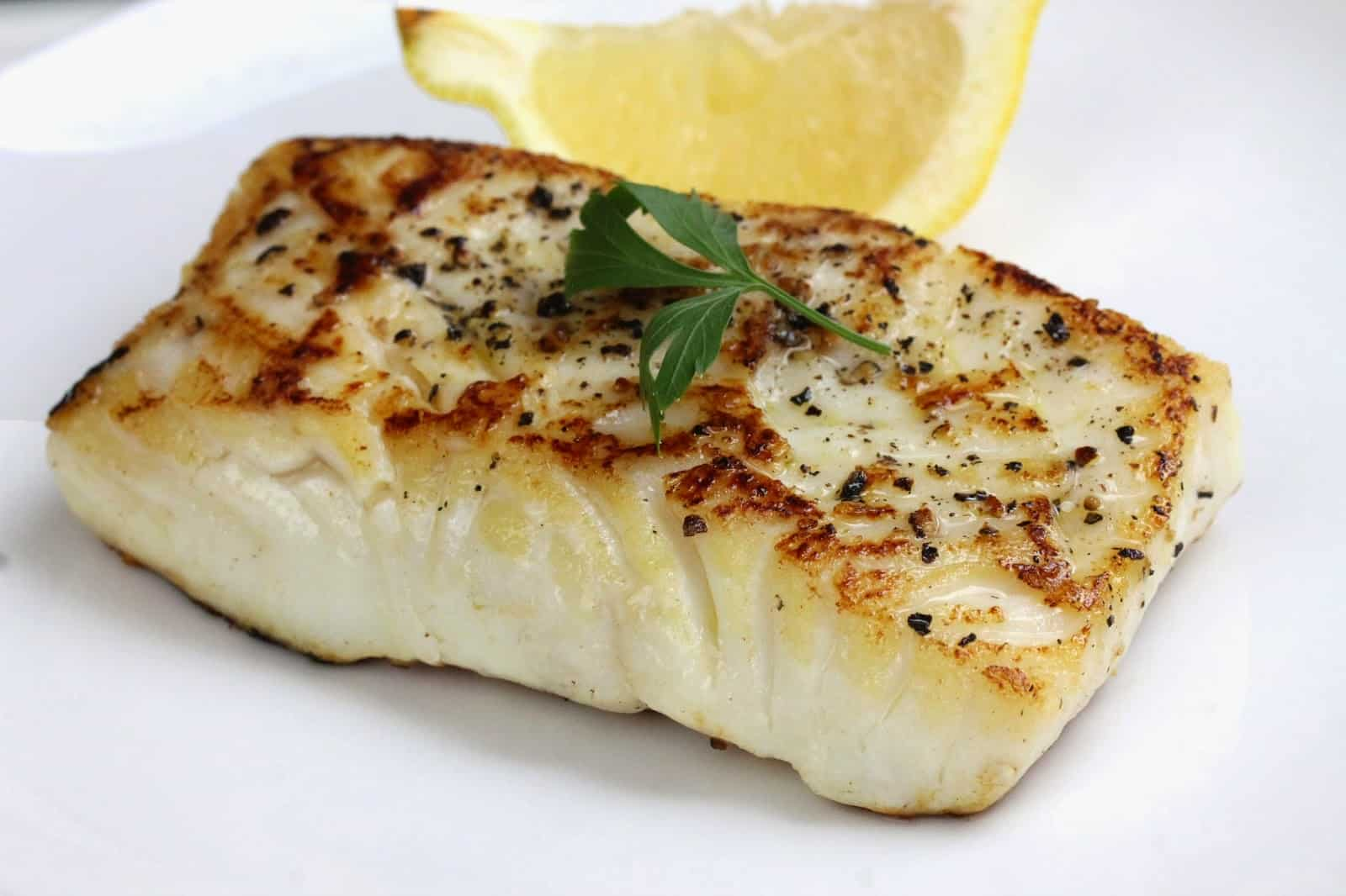 A pan seared fish filet, seasoned and ready to eat. Garnished with a parsley sprig and a lemon wedge.
