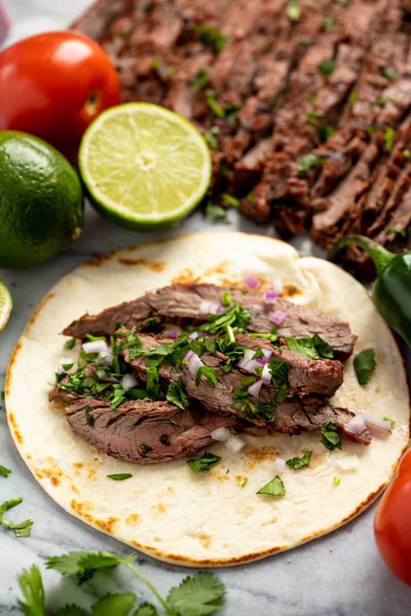 Carne Asada on a tortilla topped with onions and parsley.