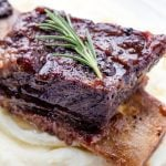 Braised Beef Short Ribs served over mashed potatoes and garnished with a sprig of rosemary