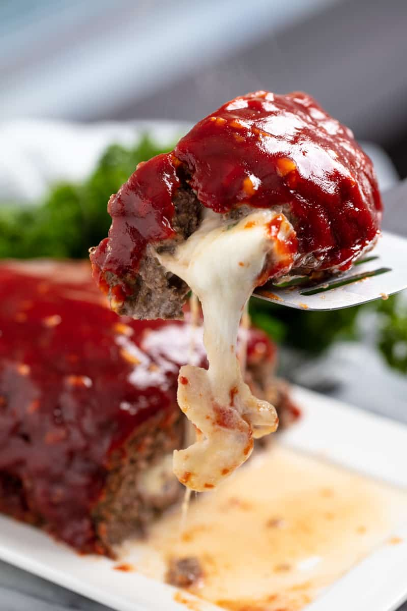 Slice of Mozzarella Stuffed Meatloaf with cheese oozing out of it being held up by a spatula.