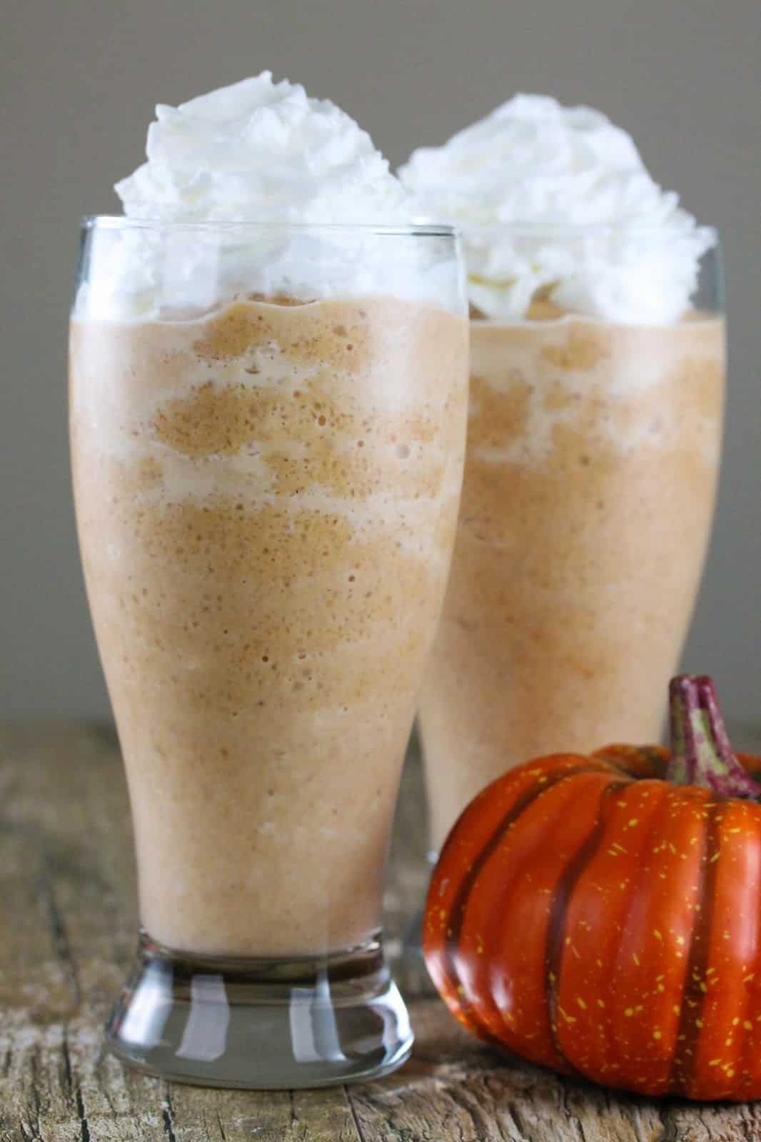 Two Pumpkin pie frappes are sitting by a fake pumpkin.