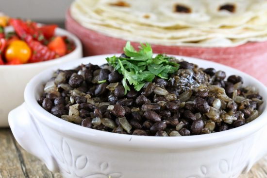 Restaurant Style Mexican Black Beans in a white bowl with tortillas and tomatoes in the background