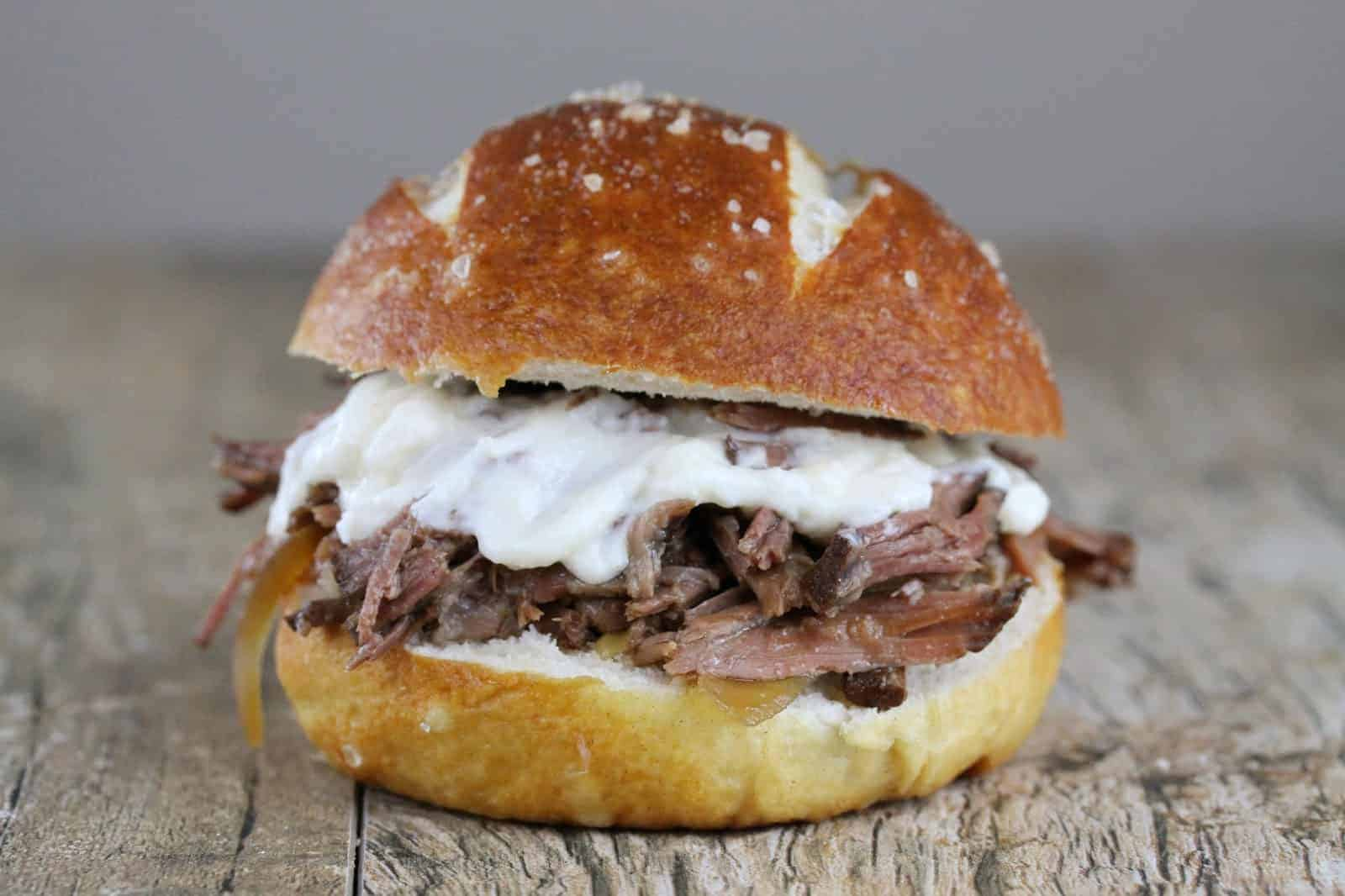 Slow Cooker Beef and horseradish sandwich with cheese on a woodentable.