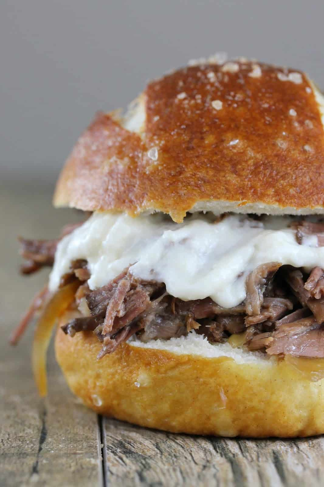 Close up of Shredded Beef and Horseradish Sandwich on a wood counter.