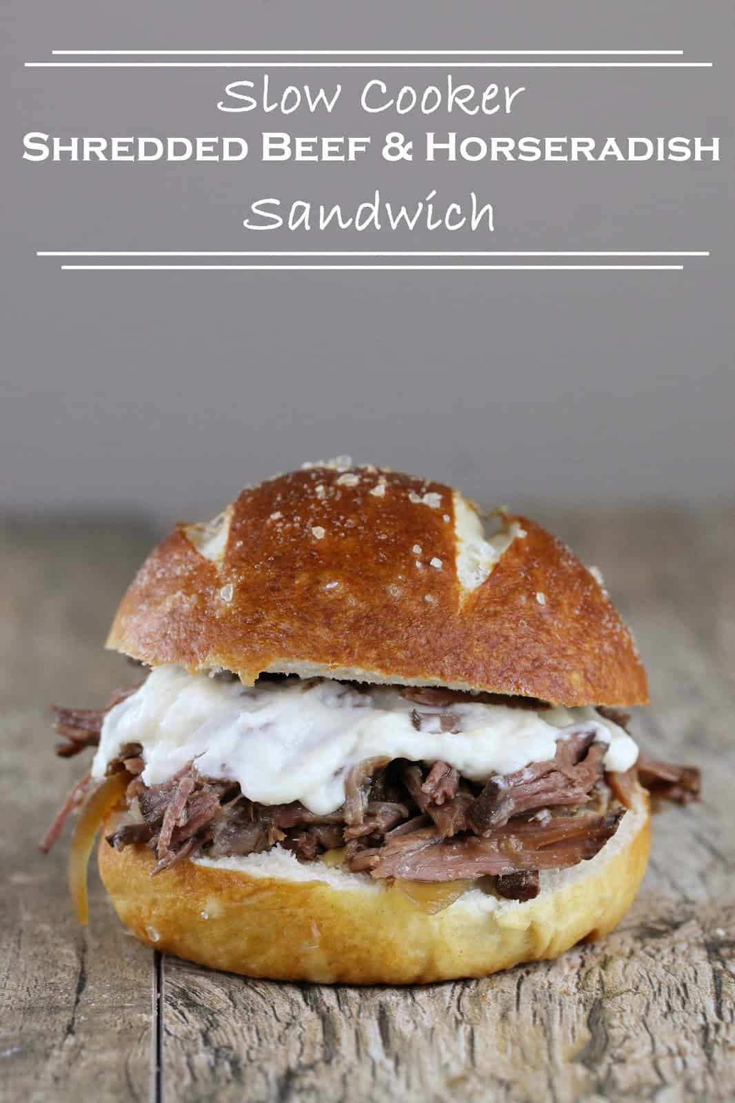 """Slow Cooker Shredded Beef and Horseradish Sandwich on a wood counter with the words """"Slow Cooker Shredded Beef and Horseradish Sandwich"""" above it."""