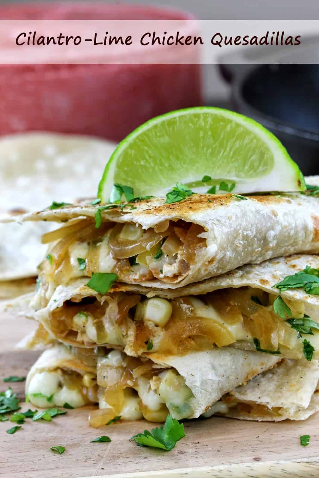 A stack of quesadillas spilling over with cheese, onions, corn and chicken and garnished with fresh cilantro and a lime wedge