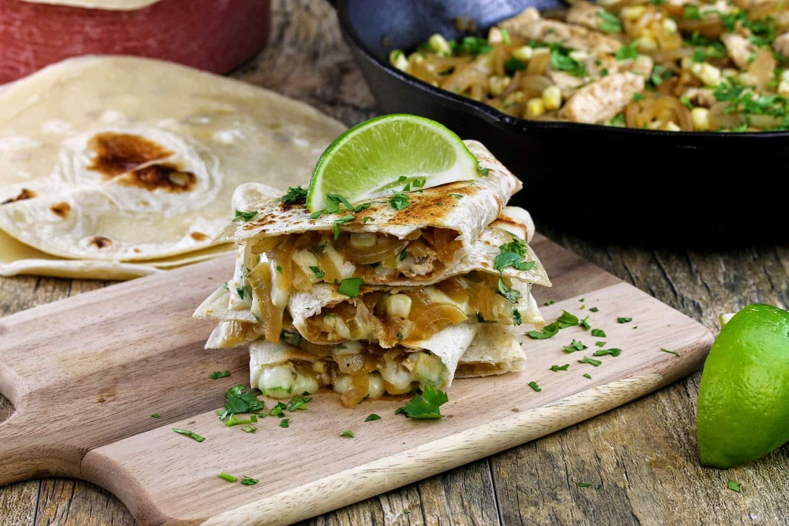 A stack of chicken-lime quesadillas spilling over with cheese, onions, corn and chicken and garnished with fresh cilantro and a lime wedge all on a cutting board.