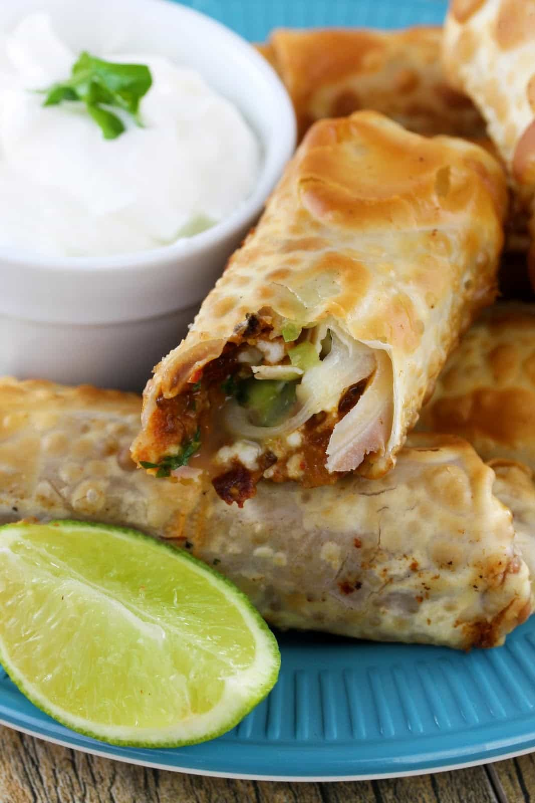 Mexican egg rolls with lime wedges on a blue plate