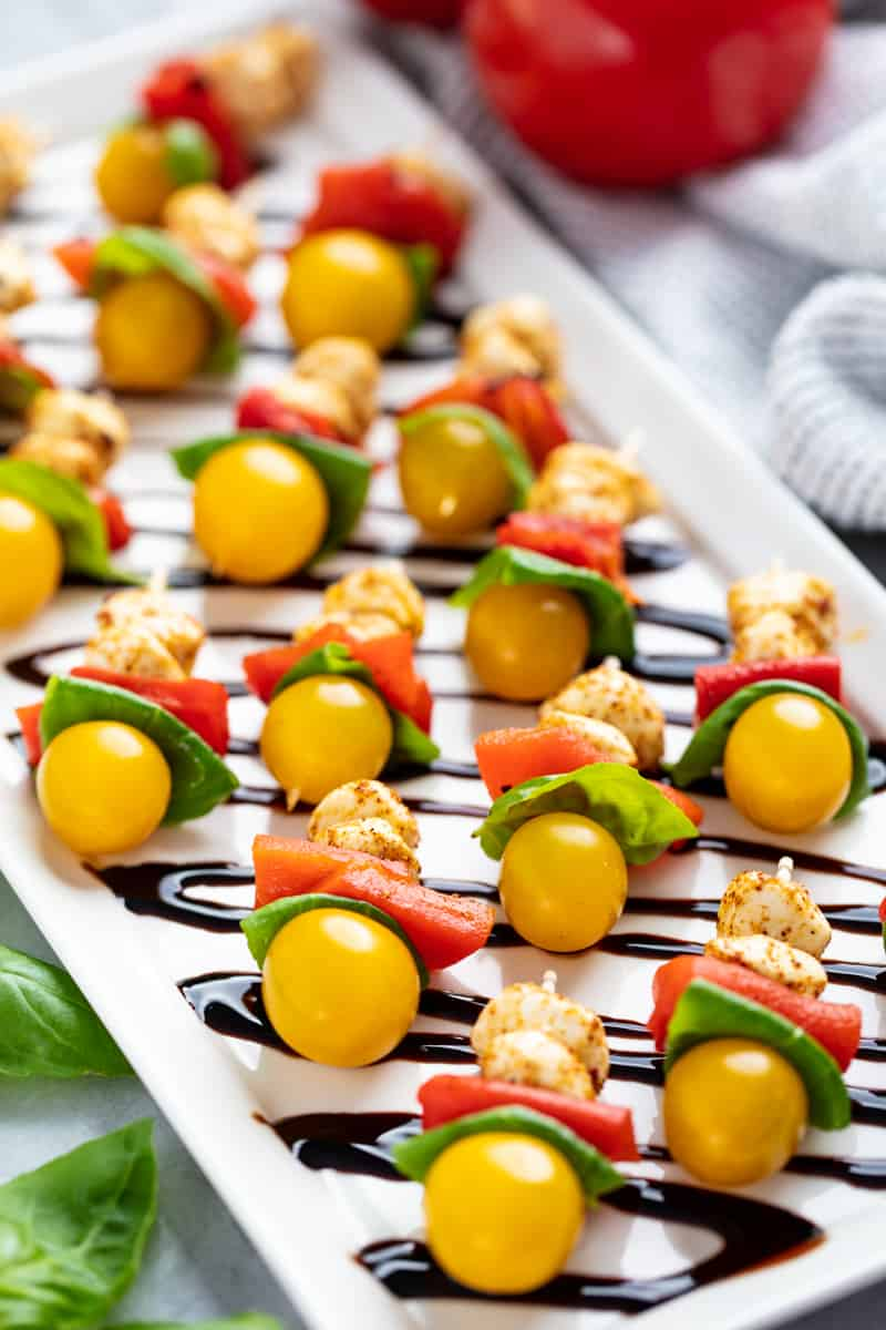 a tray of southwestern caprese bites drizzled with balsamic vinegar