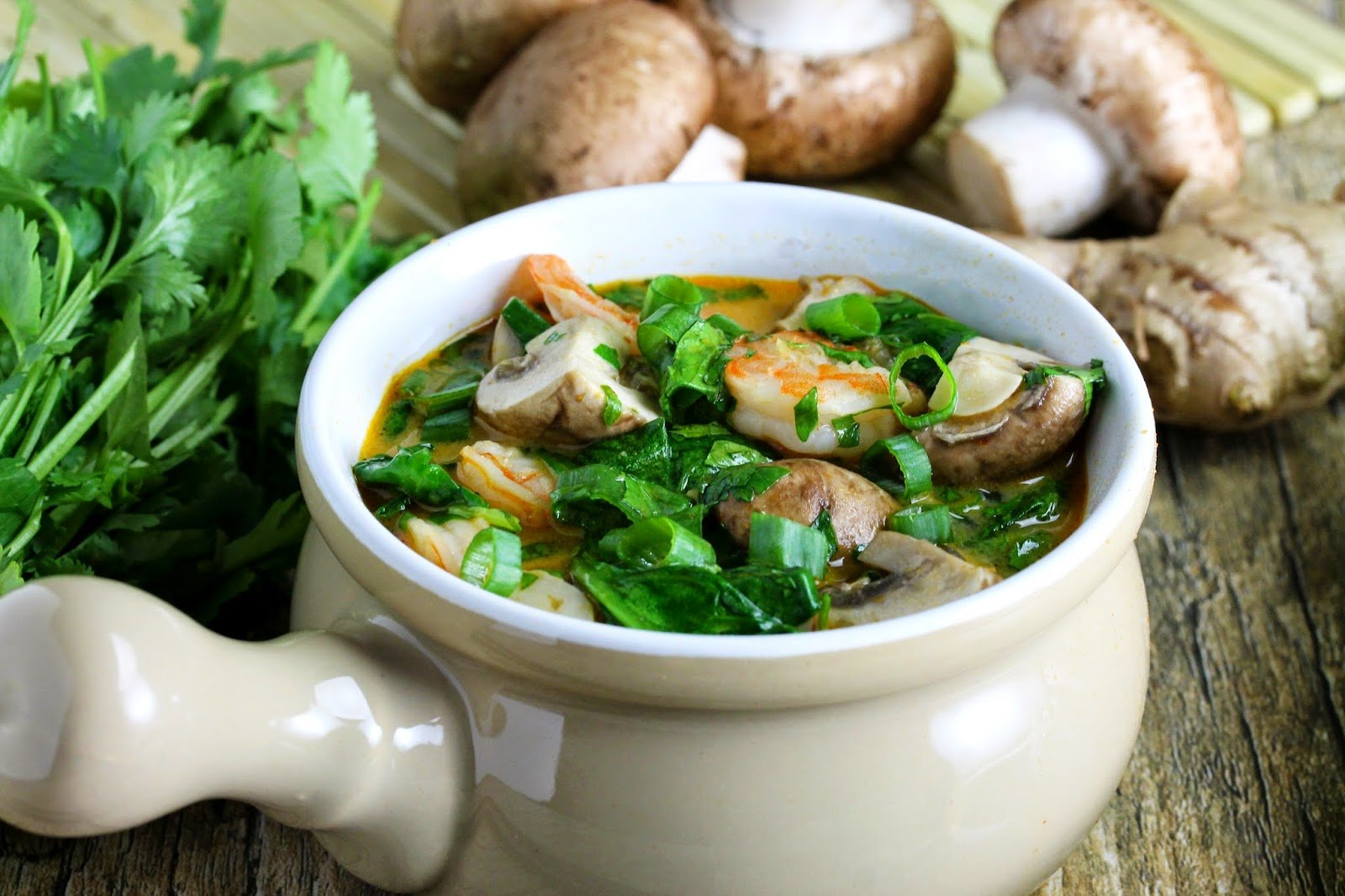 This soup is made from all fresh ingredients: A bowl of Thai Style Shrimp and Noodle Curry Soup surrounded by a bunch of fresh cilantro, crimini mushrooms and ginger