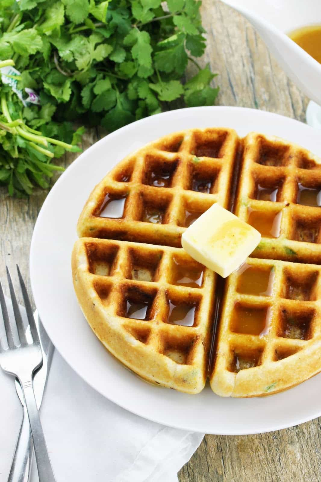 Bacon-Jalapeno Cornbread Waffles drizzled with Honey Butter Syrup and a slice of butter, the perfect combination of savory and sweet