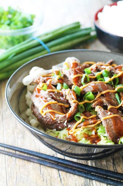Rice noodles, rice, and cabbage, topped with delicious Korean bulgogi, drizzled with sriracha mayo and Korean barbecue sauce....it's seriously so good!