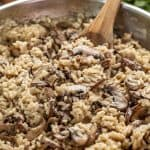 Close up Mushroom Risotto in a skillet with a wooden spoon in it.
