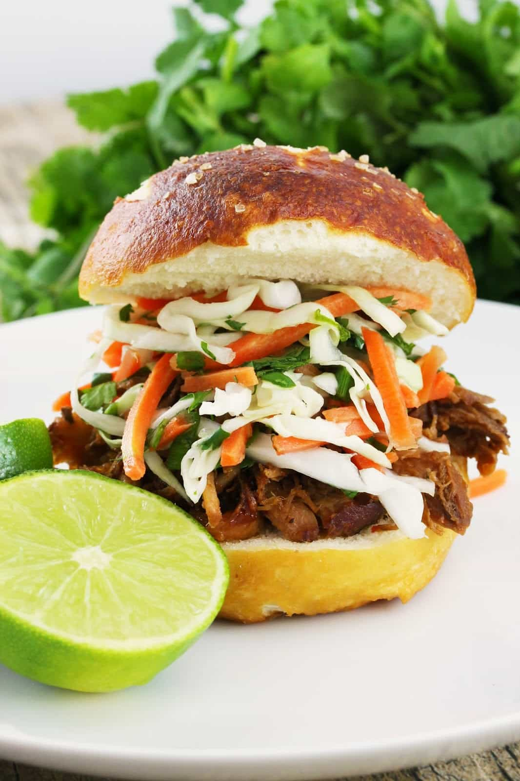 Pulled pork sandwich on a white plate topped with a Thai Slaw on a white plate