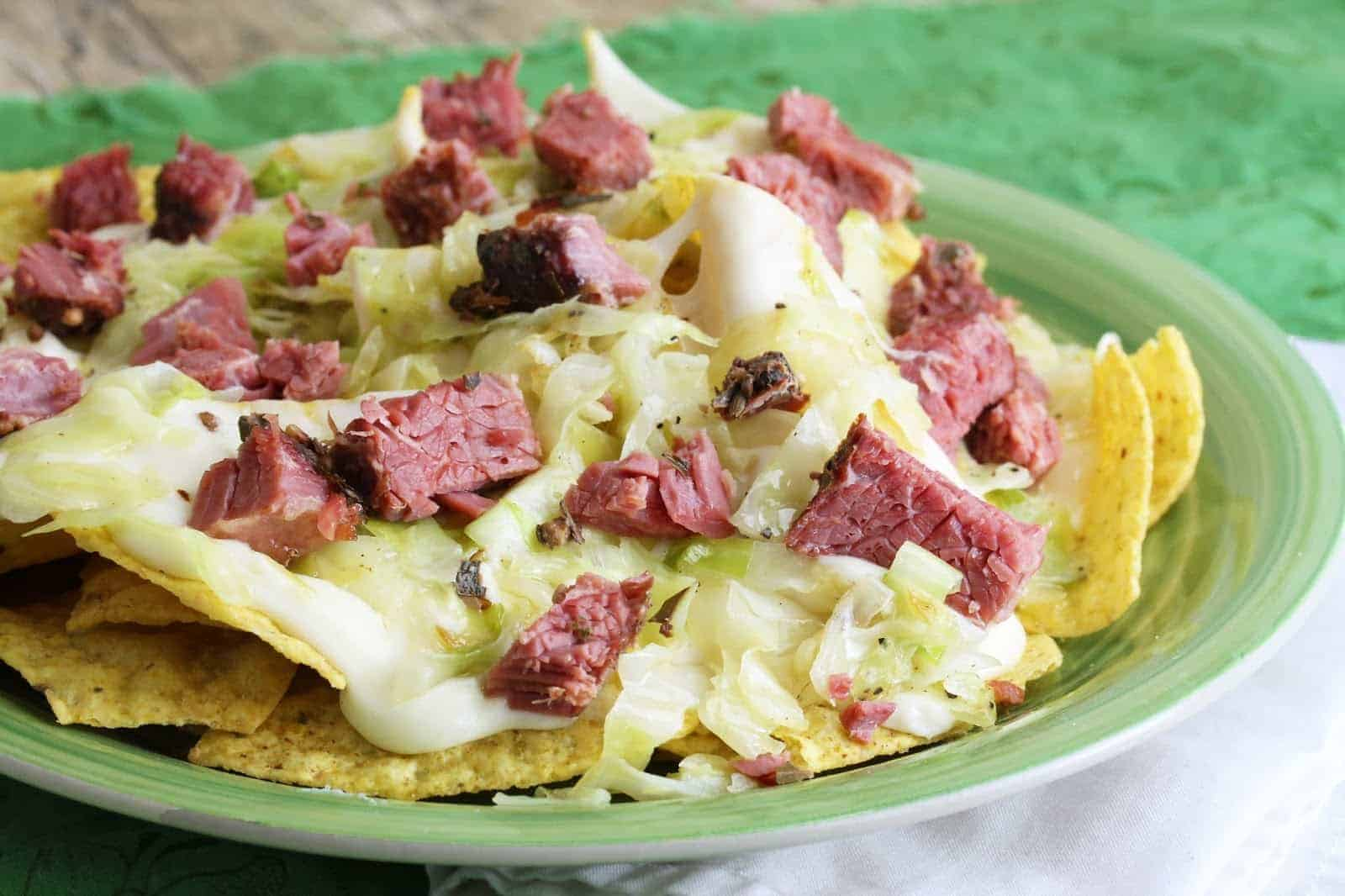 Close up of Corned beef and cabbage nachos on a green plate.