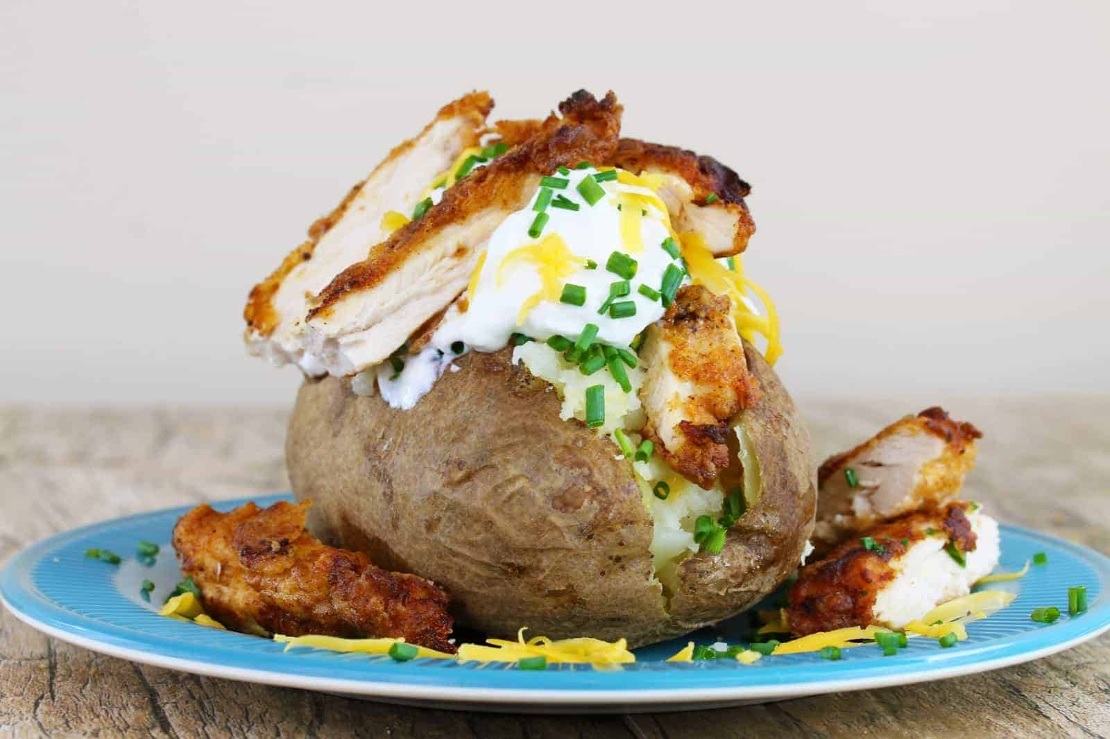 Low view of A baked potato stuffed with sour cream, cheddar cheese and fried chicken, garnished with fresh chives
