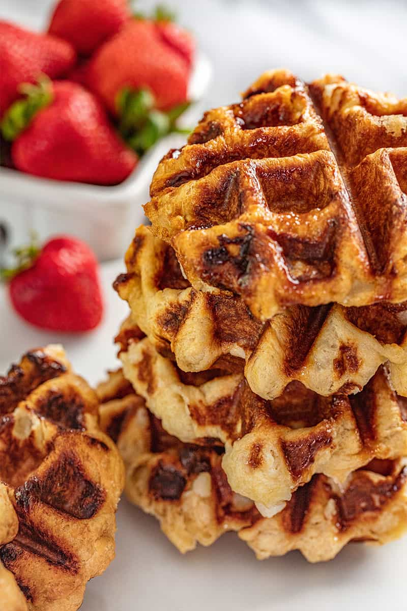 A stack of Liege Waffles with fresh strawberries in the background