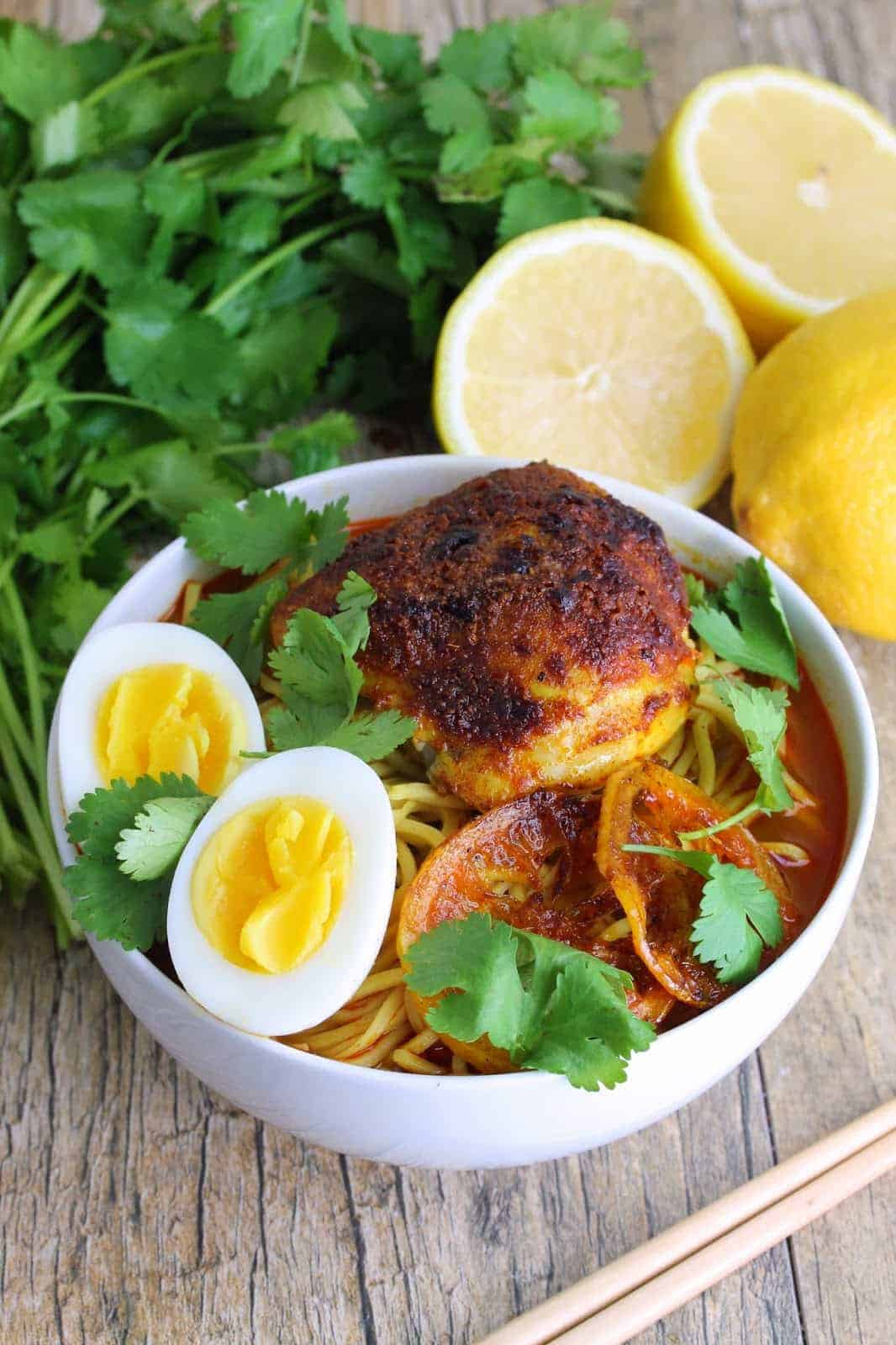 Flavorful ramen topped with a Moroccan chicken thigh, roasted lemon slices, a sliced boiled egg and garnished with fresh cilantro