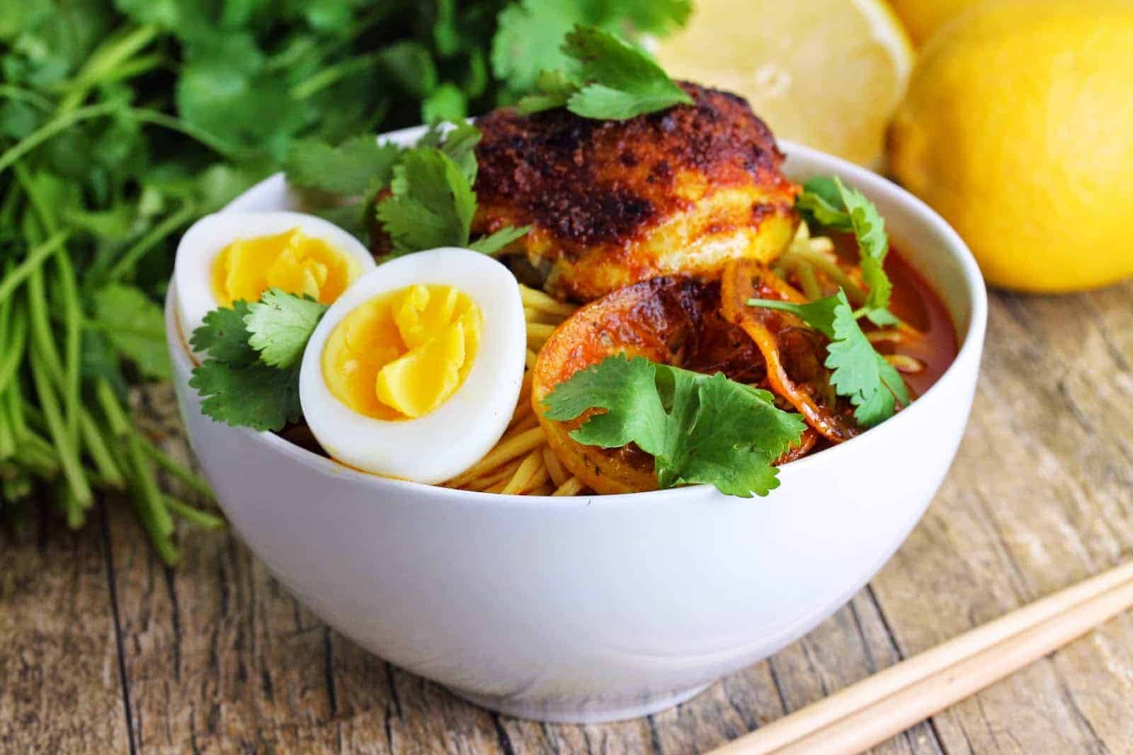 Moroccan style ramen in a white bowl topped with Moroccan chicken thighs and hard-boiled eggs.