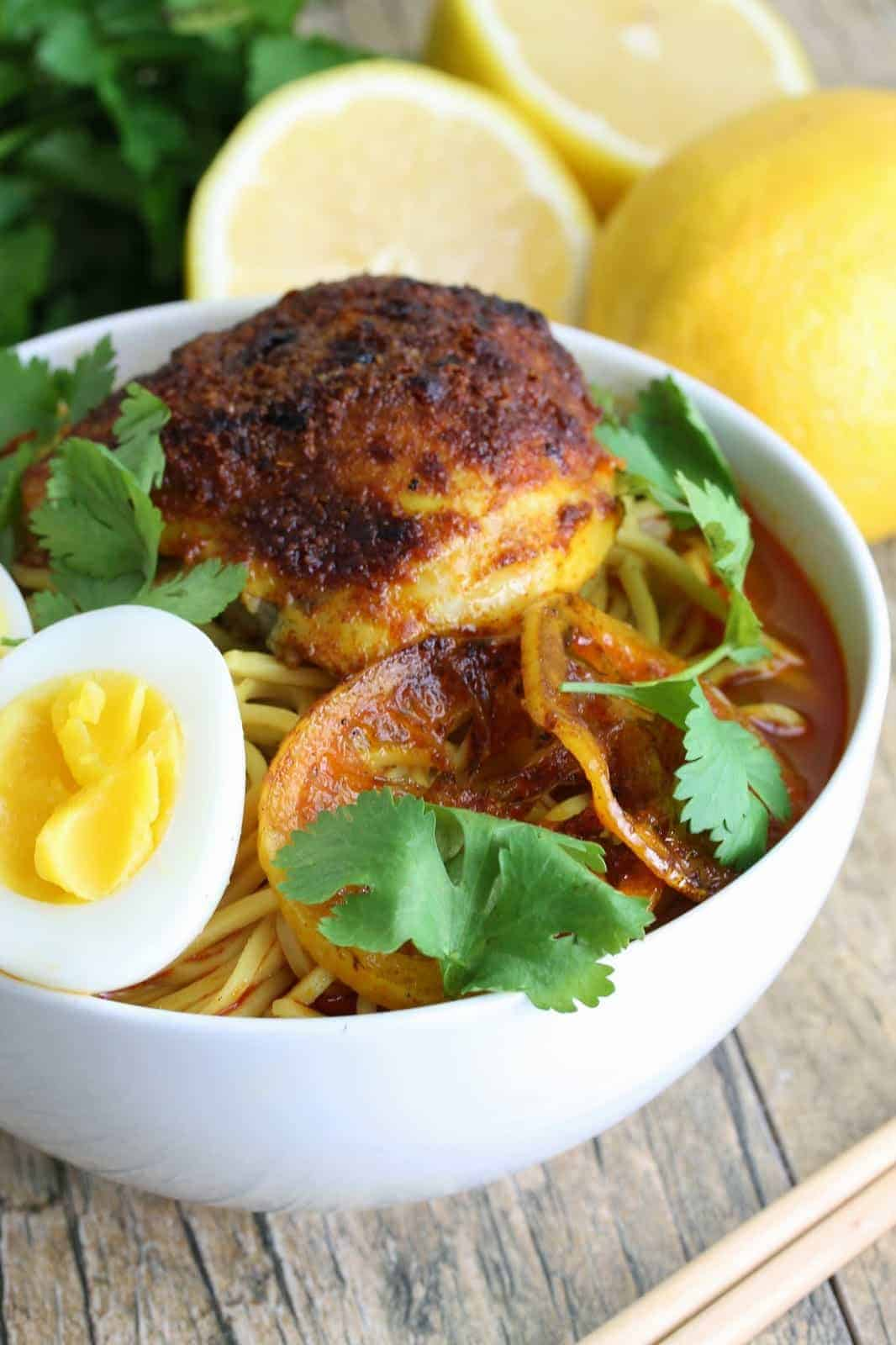 Close up of Flavorful ramen topped with a Moroccan chicken thigh, roasted lemon slices, a sliced boiled egg and garnished with fresh cilantro