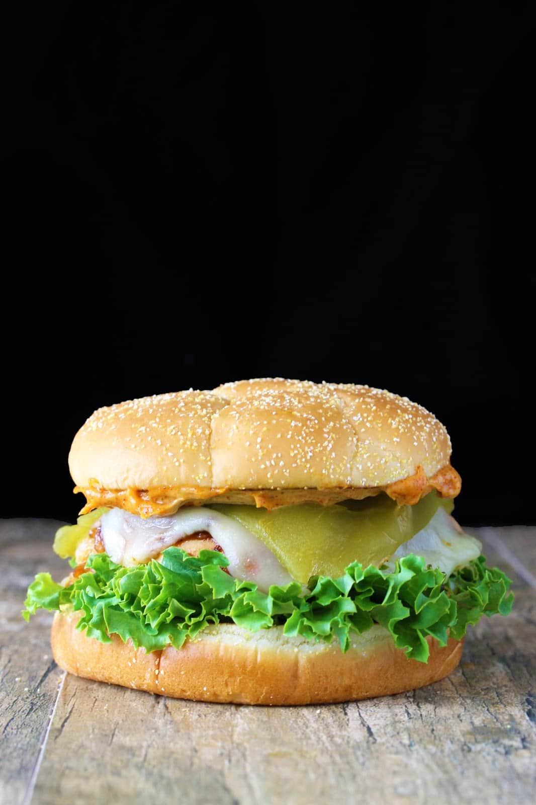 Santa fe chicken sandwich on a wooden table with a black background