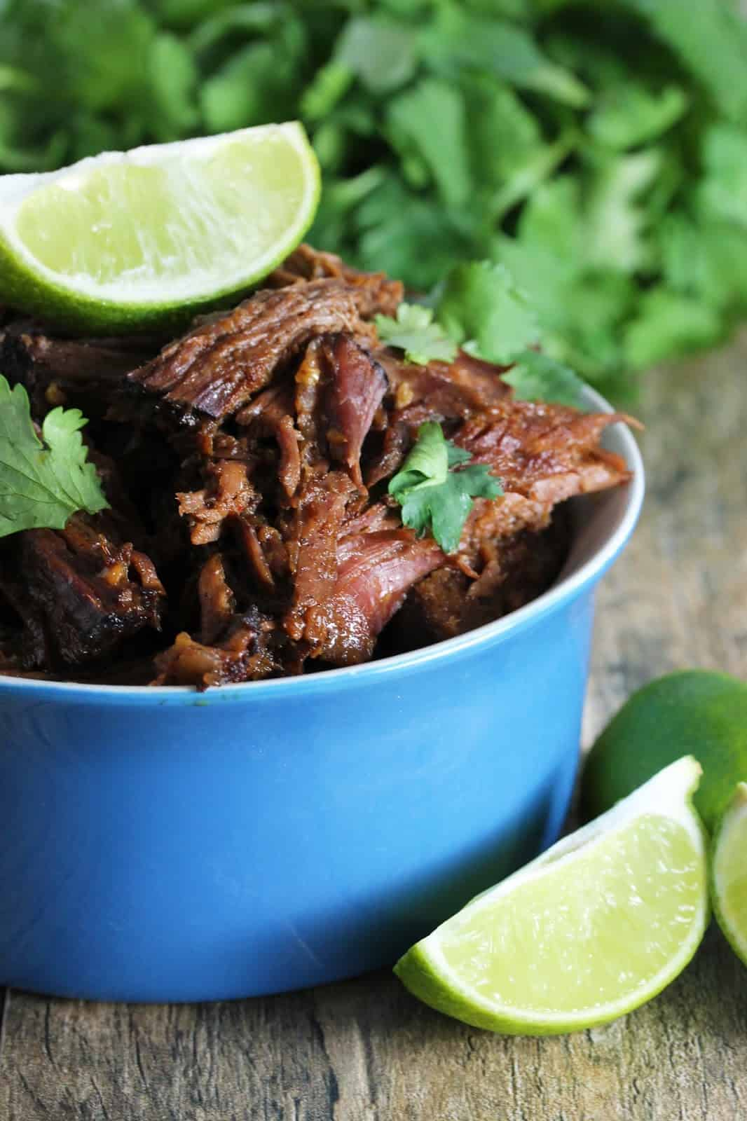 Easy Slow Cooker Chili-Lime Mexican Shredded Beef in a Crockpot, garnished with cilantro and fresh lime wedges