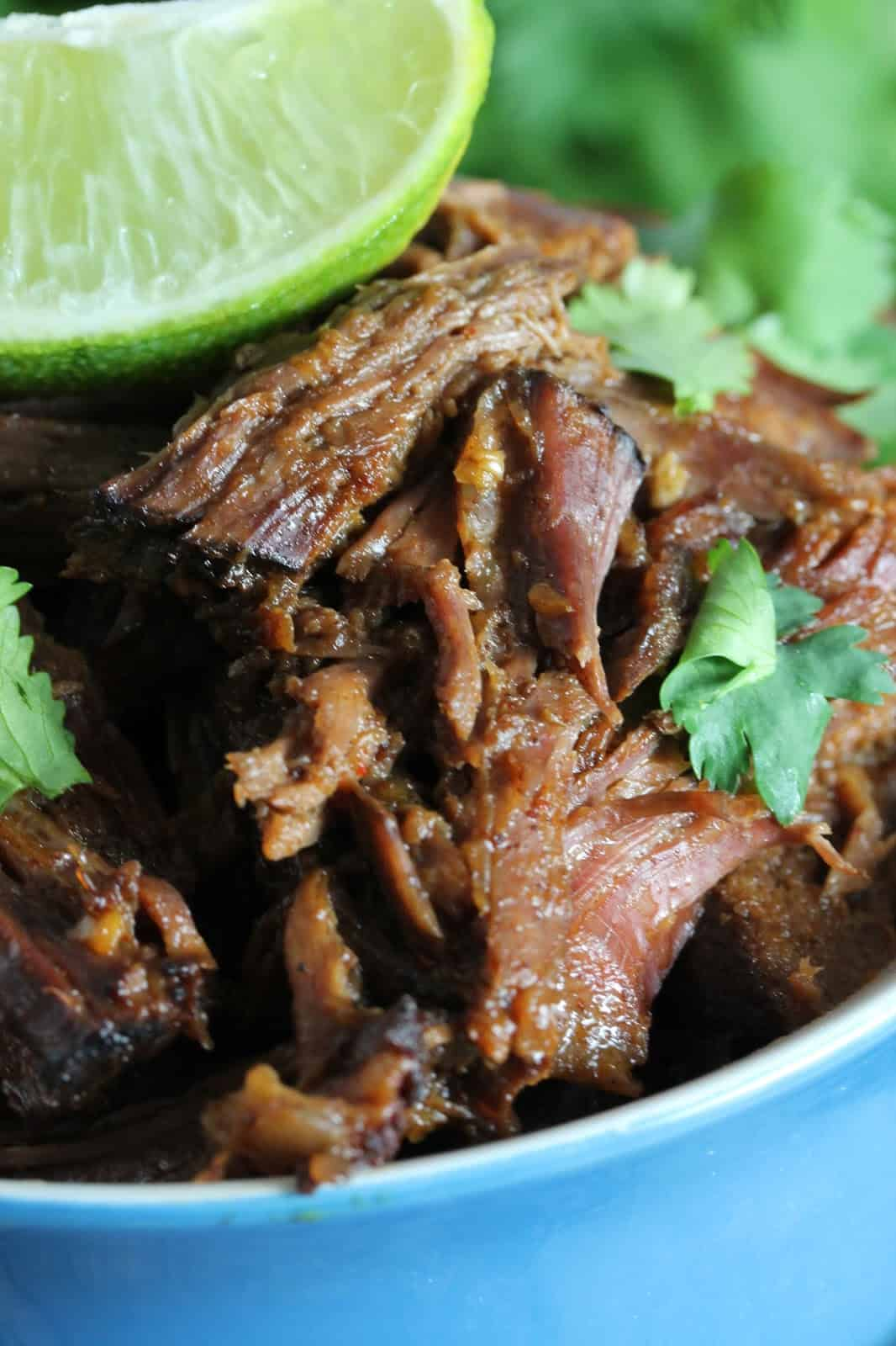 Close up of Easy Slow Cooker Chili-Lime Mexican Shredded Beef in a Crockpot, garnished with cilantro and fresh lime wedges