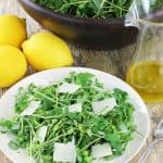 Pea shoot salad on a white plate garnished with shaved parmesan
