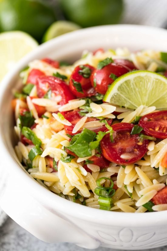 Cilantro-Lime orzo pasta salad with cilantro, lime, and cherry tomatoes in a white decorative bowl