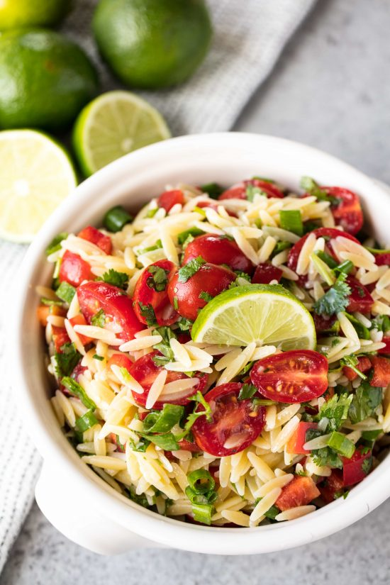 Cilantro-Lime orzo pasta salad with cilantro, lime, and cherry tomatoes in a white bowl with handles