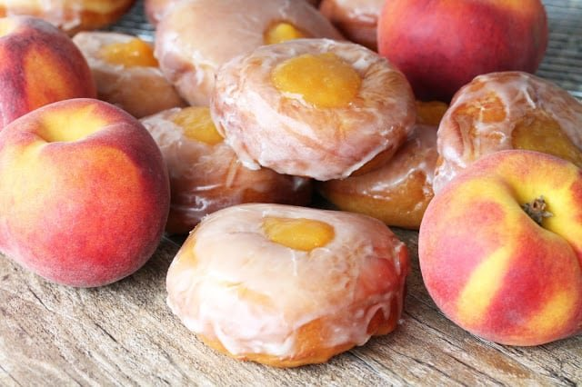 Peach pie donuts stacked next to fresh peaches