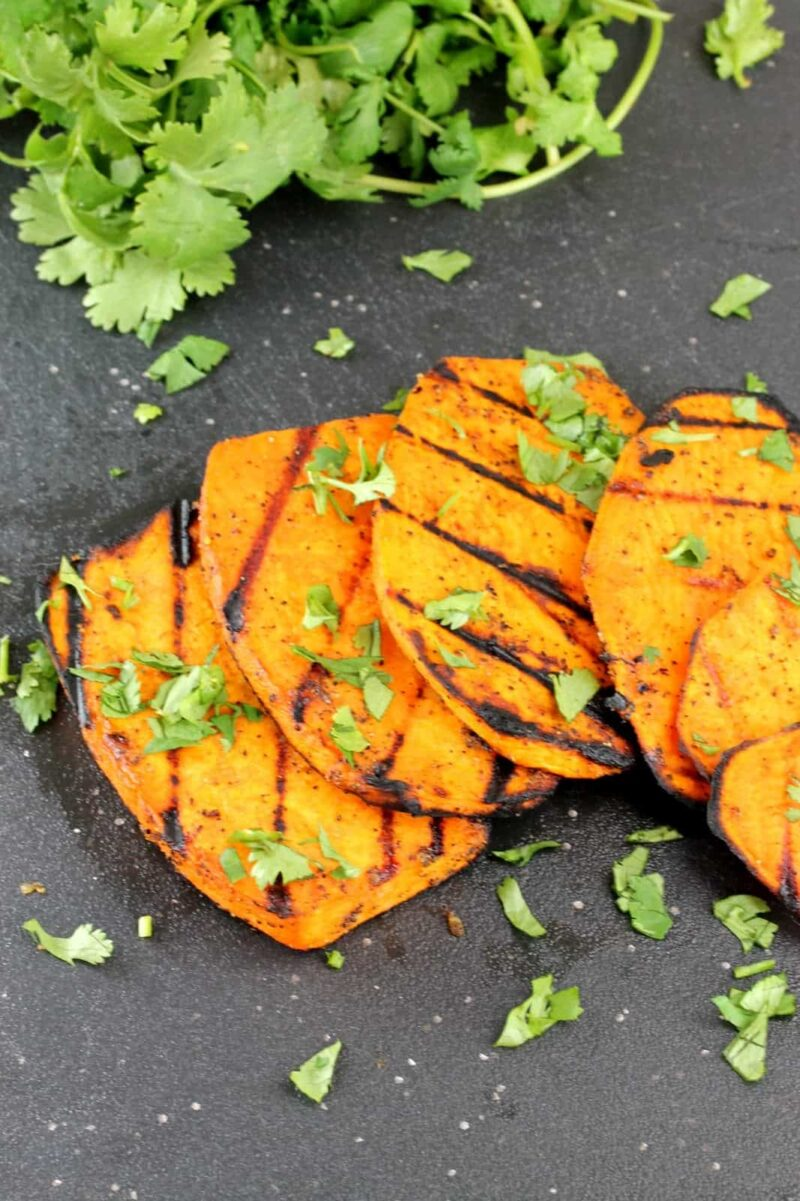 Grilled slices of sweet potatoes on a black cutting board garnished with cilantro